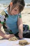 Junges Mädchen, das im Sand spielt Lizenzfreie Stockfotografie
