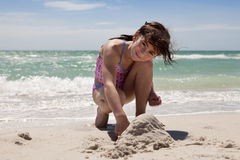 Junges Mädchen, das im Sand spielt Stockfotos