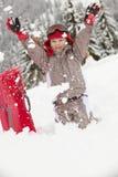 Junges Mädchen, das im Schnee mit Schlitten spielt Stockfotografie