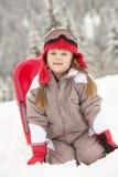 Junges Mädchen, das im Schnee mit Schlitten spielt Stockfotos