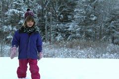Junges Mädchen, das im Schnee spielt Lizenzfreie Stockfotografie