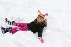 Junges Mädchen, das im Schnee spielt Stockfoto