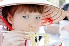 Junges Mädchen, das Isolationsschlauch in der Gaststätte isst Lizenzfreie Stockfotos