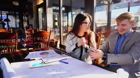 Junges Mädchen, das Jungenrichtigkeit durch Smartphone im Zeichnen von Architekturprojektdetails genießt und zeigt stock footage