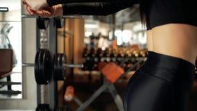 Junges Mädchen, das Körper ausdehnt Aufwärmen vor der Ausbildung Junge Frau, die Übung ausdehnend tut Anhebende Gewichte der attr stock video footage