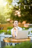 Junges Mädchen, das Kaffeestube an der im Freien unter Verwendung des Laptops sitzt lizenzfreies stockbild