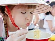 Junges Mädchen, das Koreanischart Isolationsschlauch isst (ramen) Stockbilder