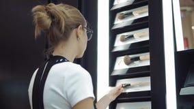 Junges Mädchen, das Kosmetik im Speicher betrachtet stock video