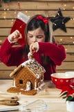 Junges Mädchen, das Lebkuchenhaus verziert stockbild