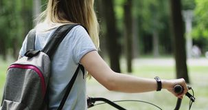 Junges Mädchen, das mit dem Fahrrad in den Händen durch den Park geht stock video