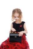 Junges Mädchen, das mit der schwarzen Tasche sitzt Stockfoto