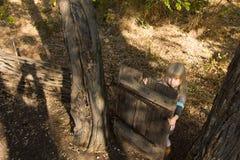 Junges Mädchen, das mit einem alten hölzernen Tor spielt Lizenzfreies Stockfoto