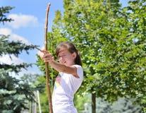 Junges Mädchen, das mit einem Pfeil und Bogen übt stockfotos