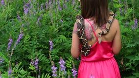 Junges Mädchen, das mit einer Schlange um seinen Hals auf der Natur aufwirft stock video footage
