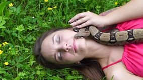 Junges Mädchen, das mit einer Schlange um seinen Hals auf der Natur aufwirft stock footage