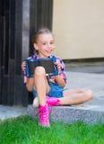 Junges Mädchen, das mit einer Tablette in den Händen sitzt Stockfotos