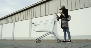 Junges Mädchen, das mit Einkaufslaufkatze vor Speicherwand geht Mädchen, das eine Kreditkarte hält und ihr intelligentes Telefon  stock video footage