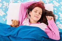 Junges Mädchen, das mit ihrem Teddybären schläft Lizenzfreies Stockfoto