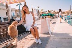 Junges Mädchen, das mit Katze spielt und am Marsaxlokk-Fischerdorf auf Malta zu Abend isst stockbilder