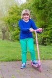 Junges Mädchen, das mit rosa Roller steht Lizenzfreie Stockfotos