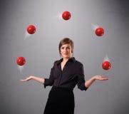 Junges Mädchen, das mit roten Bällen steht und jongliert lizenzfreies stockbild
