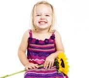 Junges Mädchen, das mit Sonnenblume lächelt Stockfotografie