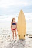 Junges Mädchen, das mit Surfbrett auf Strand steht Stockfotografie