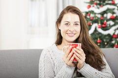 Junges Mädchen, das mit warmem Tee am Weihnachten sich entspannt Stockfoto