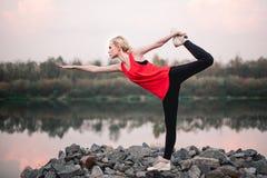 Junges Mädchen, das nahe Flusslandschaft der Yogaeignungsübung im Freien tut Abendsonnenuntergang, Haltung Namaste Lotus Meditati Lizenzfreies Stockbild