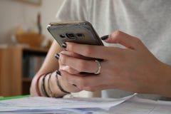 Junges Mädchen, das nahe hohe Hände des Smartphone verwendet Stockfotografie