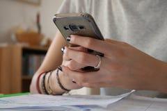 Junges Mädchen, das nahe hohe Hände des Smartphone verwendet Stockfoto
