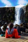 Junges Mädchen, das nahe Wasserfall in Island kühlt Lizenzfreies Stockfoto