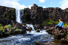Junges Mädchen, das nahe Wasserfall in Island kühlt Lizenzfreies Stockbild