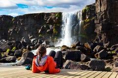 Junges Mädchen, das nahe Wasserfall in Island kühlt Stockbild