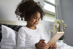 Junges Mädchen, das oben im Bett, unter Verwendung der digitalen Tablette, Abschluss lächelt Stockfotografie
