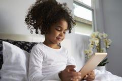 Junges Mädchen, das oben im Bett, unter Verwendung der digitalen Tablette, Abschluss lächelt Lizenzfreie Stockfotografie