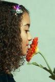Junges Mädchen, das orange Blume riecht Lizenzfreie Stockbilder