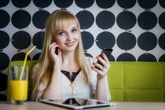 Junges Mädchen, das Orangensaft am Café trinkt Stockfotos