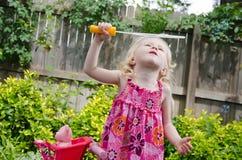 Junges Mädchen, das playfully Luftblasen durchbrennt Stockfotos
