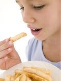 Junges Mädchen, das Pommes-Frites isst lizenzfreies stockbild
