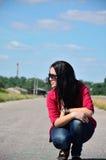 Junges Mädchen, das am Rand der Straße sitzt Stockfotografie