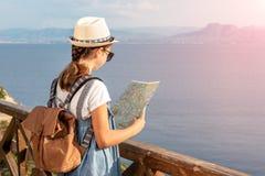 Junges Mädchen, das Reisekarte in den Bergen nahe dem Meer betrachtet lizenzfreies stockbild