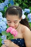 Junges Mädchen, das rosafarbene Blume riecht Stockfoto