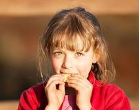 Junges Mädchen, das Scheibe der Gurke isst Stockbild