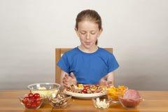 Junges Mädchen, das selbst gemachte Pizza bildet lizenzfreies stockbild