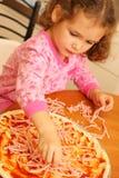 Junges Mädchen, das selbst gemachte Pizza zubereitet Lizenzfreie Stockbilder