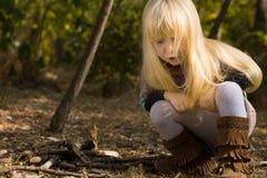 Junges Mädchen, das sich draußen im Herbst duckt Stockfotografie