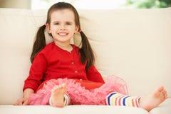 Junges Mädchen, das sich zu Hause auf Sofa entspannt Lizenzfreies Stockbild