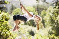 Junges Mädchen, das Spaß auf Seil-Schwingen hat stockfotos