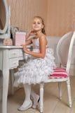 Junges Mädchen, das am Spiegel beim Schlafzimmerlächeln sitzt Stockbild